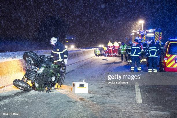 Rescuers stand next to a turned over Quad at the scene of an accident on the snowcovered Autobahn A5 at the Bad Homburger Kreuz motorway intersection...