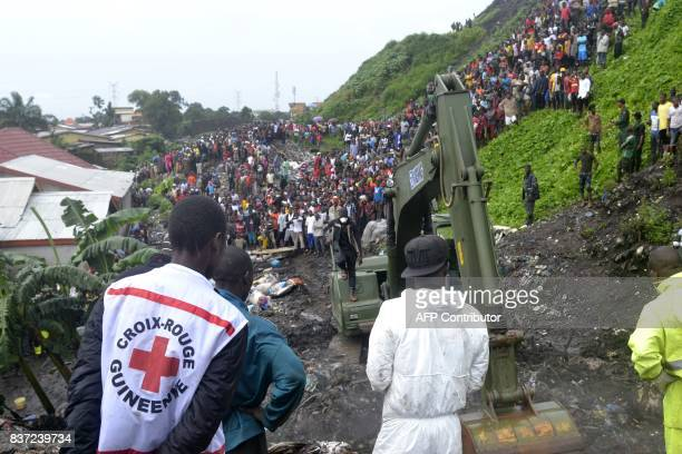 Rescuers stand on the site where eight people died and dozens were injured in the West African state of Guinea when a rubbish dump on the outskirts...