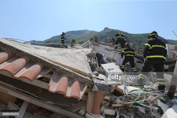 Rescuers team walk near a house, destroyed in the earthquake in one of the more heavily damaged areas on August 22, 2017 in Casamicciola Terme,...