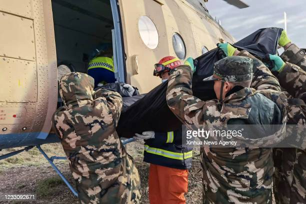 Rescuers transfer the remains of victims to a helicopter in Jingtai County of Baiyin City, northwest China's Gansu Province, May 23, 2021. Lasting...