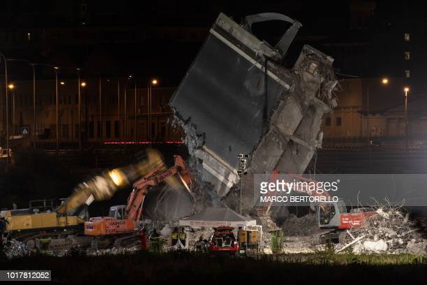 TOPSHOT Rescuers use heavy machinery as they work among the rubble and wreckages of the Morandi motorway bridge two days after a section collapsed in...