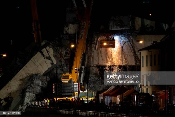 Rescuers use heavy machinery as they work among the rubble and wreckages of the Morandi motorway bridge two days after a section collapsed in Genoa...