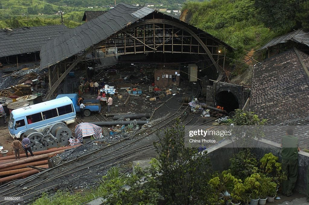 Rescuers wait outside a pit to remove bodies of dead miners at the Daxing Colliery where a flood trapped over 100 miners, August 15, 2005 in Xingning of Guangdong Province, south China. Two more bodies of trapped miners were found on August 15, with 120 still missing. Heavy rain has led to increased difficulties for rescuers to find the rest miners. Experts at the site said, there is now almost no hope of finding the trapped miners alive after more than eight days underground, according to state media.