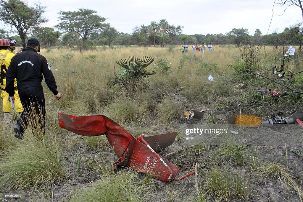 Rescuers walk amid the debris of the helicopter that transported former Paraguayan general and UNACE party presidential candidate Lino Oviedo and crashed on the eve, at Estancia La Mocha, Chaco, Paraguay, on February 3, 2013. All three passengers of the aircraft --Ovideo, his bodyguard and the pilot-- died in the accident. AFP PHOTO/Roque GONZALEZ