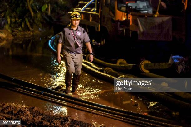 A rescuers walk between the hoses which are carrying water out of Tham Luang Nang Non cave on July 05 2018 in Chiang Rai Thailand The 12 boys and...