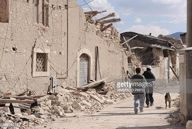 Rescuers walk on April 6, 2009 past a collapsed house in Onna, a small town some 10 kilometers from L'Aquila, epicentre of an earthquake which jolted...