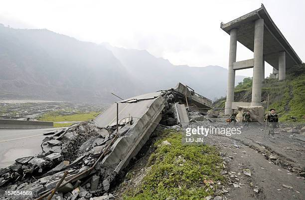 Rescuers walk past a collapsed bridge outside Yingxiu of Wenchuan county after a quake with a magnitude of 78 rocked China on May 11 in the...
