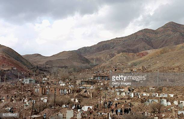 Rescuers wander among the remains of collapsed buildings looking for survivors on February 24 2005 in the ruins of the hillside village of Dahouyeh...