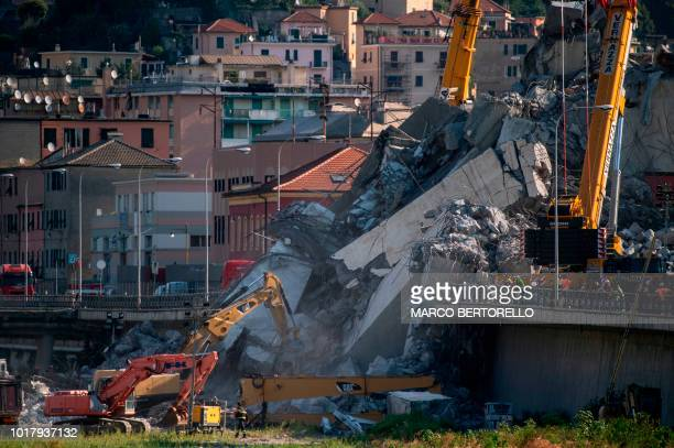 Rescuers work among the rubble and wreckage of the Morandi motorway bridge in Genoa on August 17 three days after a section collapsed Rescue workers...