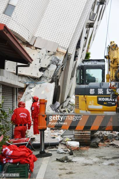 Rescuers work at a building slanting on its side in Hualien Taiwan on Feb 7 a day after a magnitude 64 earthquake struck the east coast of the island...