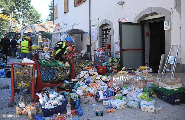 Rescuers work at a damaged store in the central Italian village of Amatrice on August 24 2016 after a powerful earthquake rocked central Italy A...