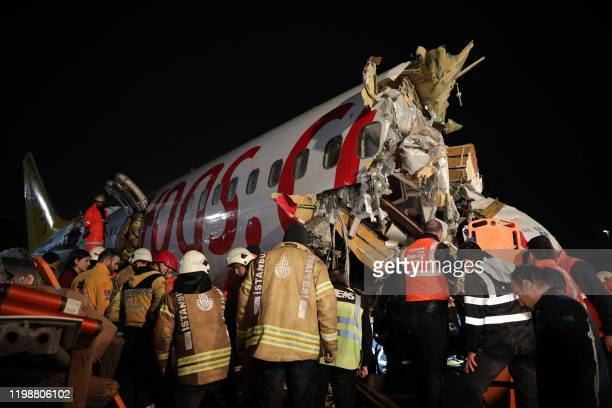 Rescuers work at the crash of a Pegasus Airlines Boeing 737 airplane after it skidded off the runway upon landing at Sabiha Gokcen airport in...