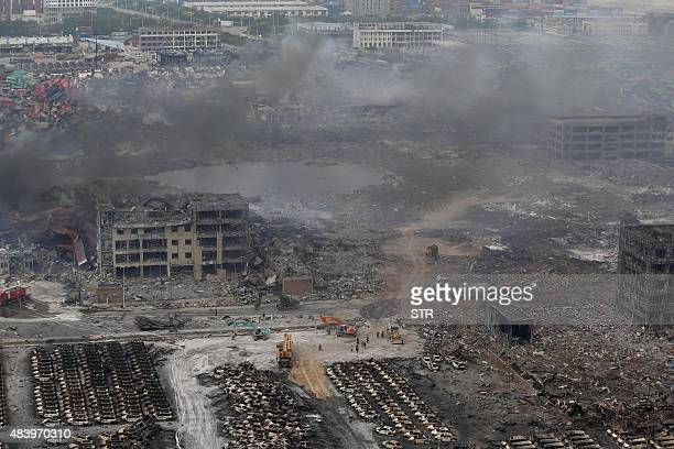 Rescuers work at the site of the explosions in Tianjin on August 14 2015 Enormous explosions in a major Chinese port city killed at least 44 people...