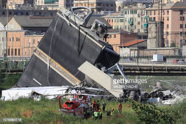 TOPSHOT Rescuers work at the site where the Morandi motorway bridge collapsed in Genoa on August 14 2018 At least 30 people were killed on August 14...