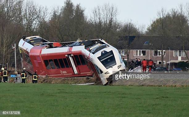 Rescuers work near a derailed passenger train after a crash with a milk tanker near Winsum on November 18 2016 Several people were hurt on November...