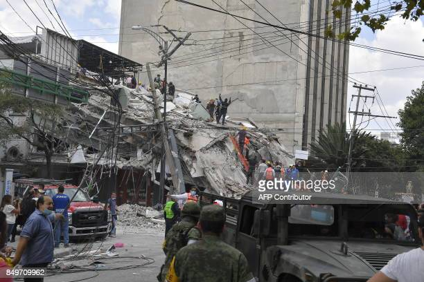 Rescuers work on the rubble from a building knocked down by a powerful quake in Mexico City on September 19 2017 A powerful earthquake shook Mexico...