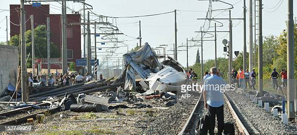Rescuers work on the site of a collision between a truck and a train killing one person and injuring other on September 24 2012 in the southern city...