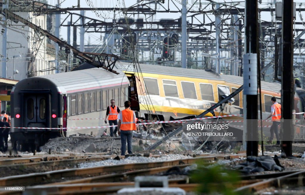 Rescuers work on the site of a train accident in the railway station of Bretigny-sur-Orge on July 12, 2013 near Paris. At least seven people were dead and dozens injured after a speeding train split in two and derailed at a station in the southern suburbs of Paris, officials said.