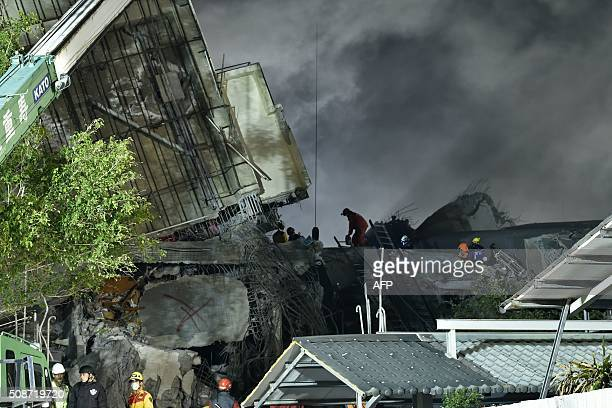 TOPSHOT Rescuers work over rubble at the site of a collapsed building in the southern Taiwanese city of Tainan on February 6 2016 following a strong...