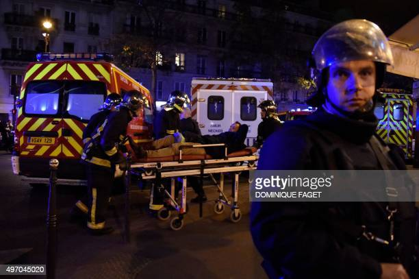 Rescuers workers evacuate a man on a stretcher near the Bataclan concert hall in central Paris, on November 13, 2015. A number of people were killed...