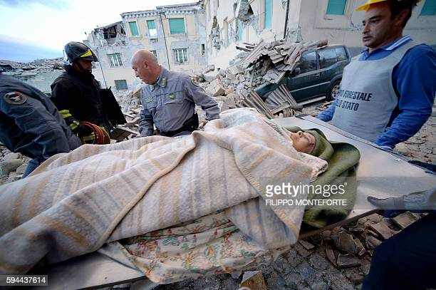 TOPSHOT Rescues carry a man in Amatrice on August 24 2016 after a strong heartquake Central Italy was struck by a powerful 62magnitude earthquake in...