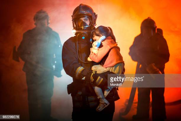 rescuing from fire - firefighter stock pictures, royalty-free photos & images