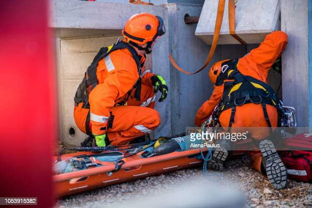 rescuing injured person from the ruins, firefighters rescue operation - rescue stock pictures, royalty-free photos & images