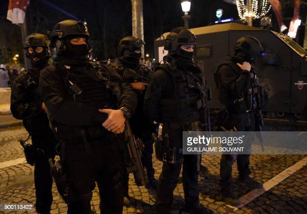 Research and Intervention Brigade officers gather as they prepare to patrol at the Champs Elysees avenue before New Year celebrations begin in Paris...