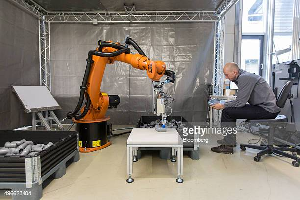 A research assistant uses a control panel to operate a Kuka KR 16 robotic arm manufactured by Kuka AG fitted with a Scape Technologies 3D camera at...