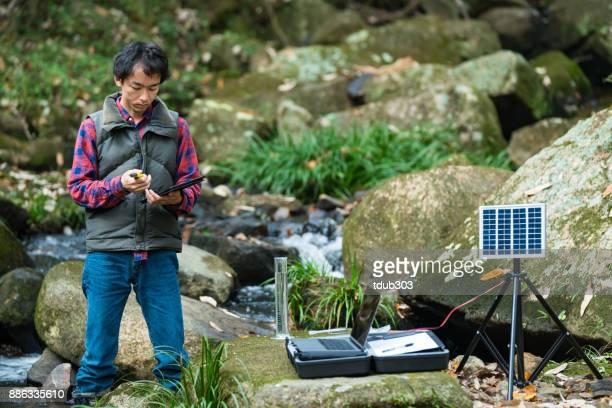 太陽動力を与えられたフィールド研究所で川の水の水質をチェックする研究員