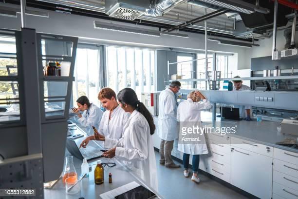 researcher discussing with colleague in laboratory - laboratório imagens e fotografias de stock