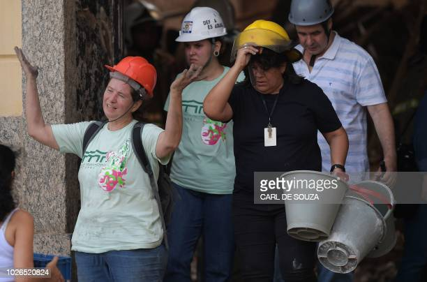 TOPSHOT A researcher gestures they try to salvage artifacts from the debris a day after a massive fire ripped through Rio de Janeiro's treasured...