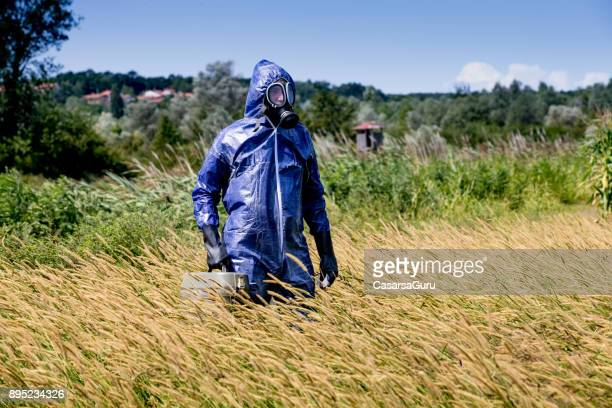 Researcher in Protective Suit on a Meadow