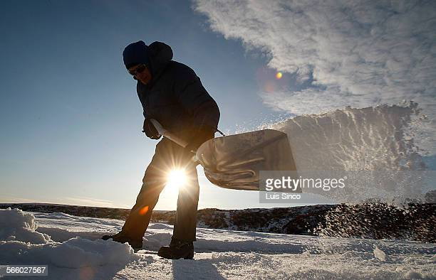 Researcher Laurence Plug shovels snow from the surface of a frozen tundra lake in search of telltale formations of frozen bubbles that indicate a...