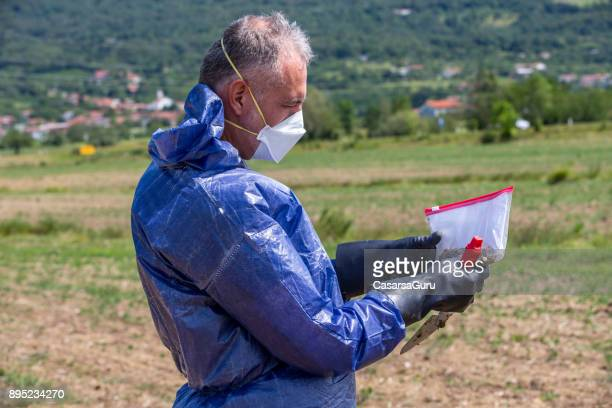 Researcher Looking at Dirt Sample on a Field
