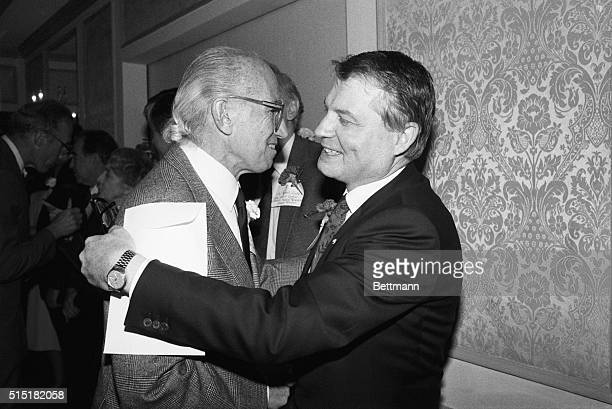 AIDS researcher Luc Montagnier hugs Jonas Salk developer of the polio vaccine after they were both presented medical research awards by the Albert...