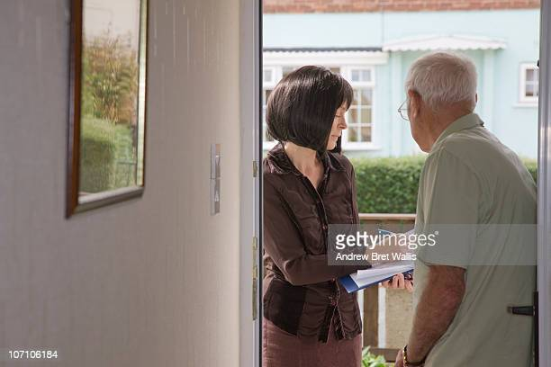 researcher talking to elderly man on the doorstep - sale stock pictures, royalty-free photos & images