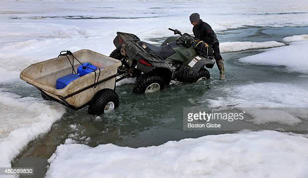 Researcher technician Josh Jones worked to get his ATV out of water on the ice near Barrow Alaska