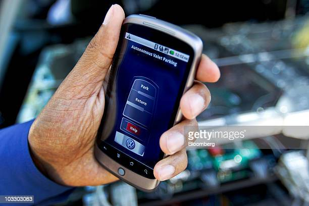 A researcher uses a Google Nexus One Android smartphone to operate a Volkswagen AG autodriving Passat wagon that can park itself which was developed...