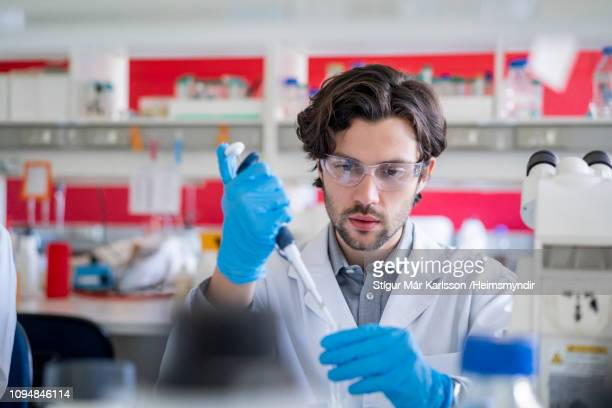 researcher using automatic pipette in laboratory - pipette stock pictures, royalty-free photos & images