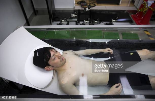 Researcher, wearing active marker motion sensors and electrodes for an electroencephalogram, lies in a tank of water while conducting bathing tests...