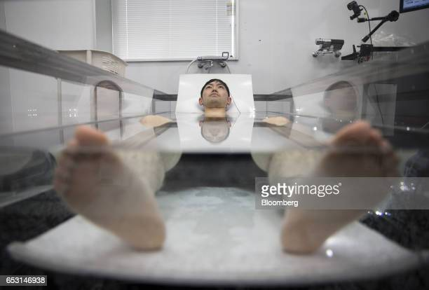 A researcher wearing active marker motion sensors and electrodes for an electroencephalogram lies in a tank of water while conducting bathing tests...
