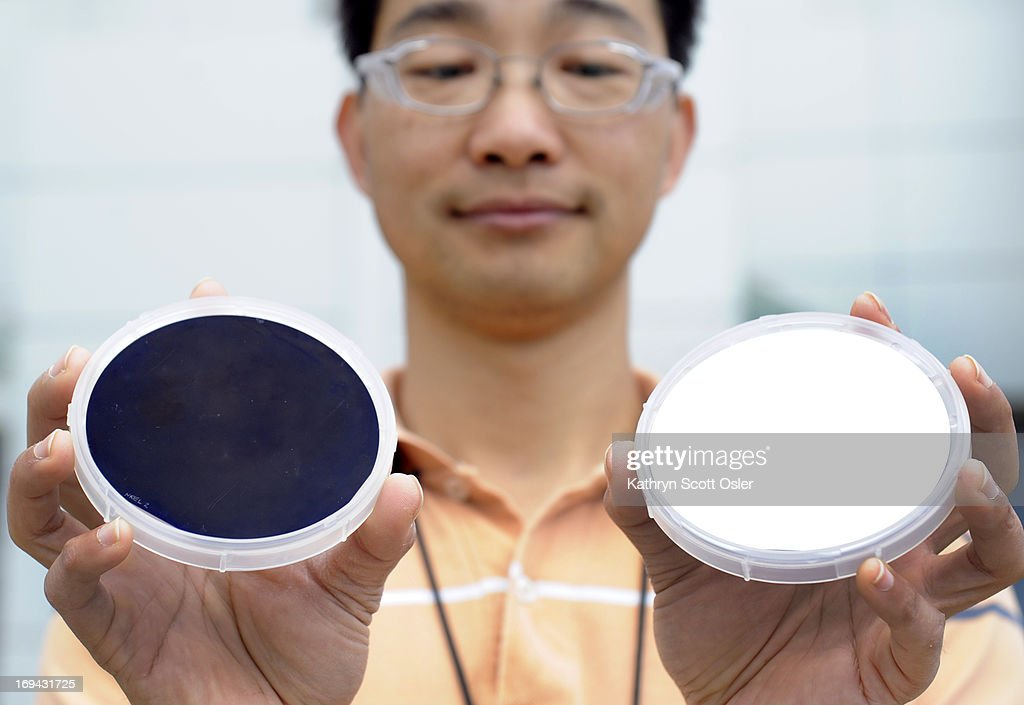 Researchers at the National Renewable Energy Lab, NREL, has developed a process called 'dark solar' that will cut the reflectivity of solar panels which will boost their energy output. A researcher on the project, Hao-Chih Yuan, holds small round disks of the dark silicon. The one on the right is before it goes through the chemical process and appears as shiny as a mirror. The sample on the left is after it is put through the process and it appears nearly black with more of a matte finish.