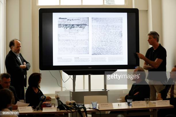 Researchers speak near a screen displaying pages of the diary of Anne Frank as the Anne Frank House publishes unknown text of the young Jew who hid...