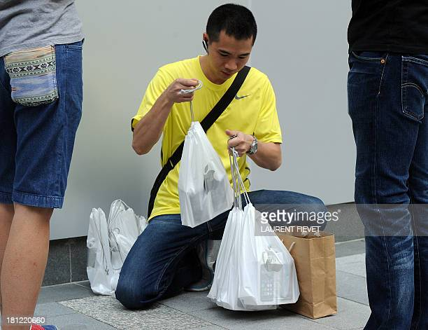 A reseller bags his newly purchased iPhones 5s handsets outside an Apple store in Hong Kong on September 20 2013 Apple acolytes got their hands on...