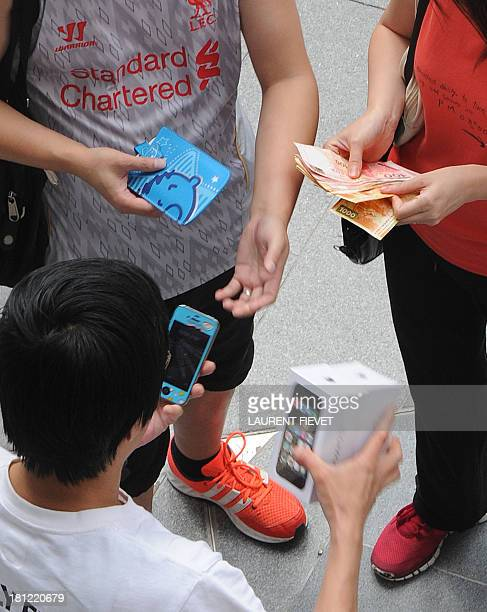 A reseller buys new iPhones 5s from new iPhone owners outside an Apple store in Hong Kong on September 20 2013 Apple acolytes got their hands on new...