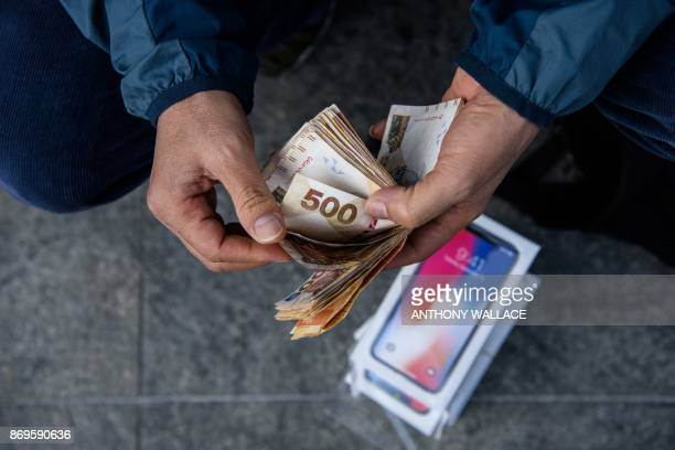 A reseller counts cash over a pile of iPhone X's near an Apple store in Hong Kong on November 3 2017 Apple profits soared by a fifth as its flagship...