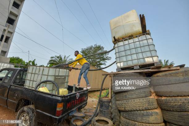 A reseller of water fills a jerrycan on a truck in the popular district of Yopougon where inhabitants lack of of drinking water in Abidjan on March...