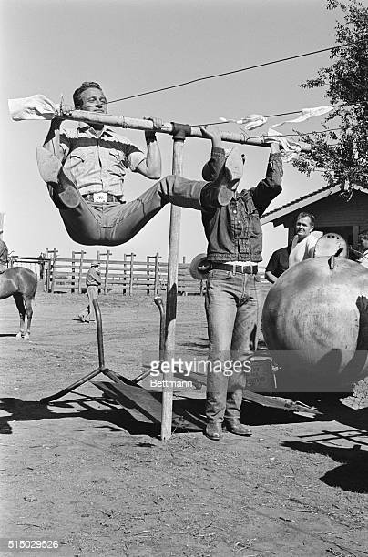 Resembling someone about to land in a saddle actor Paul Newman does his chinning with the greatest of ease on this makeshift chinning bar This is how...