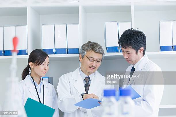 Reserch scientists looking at file